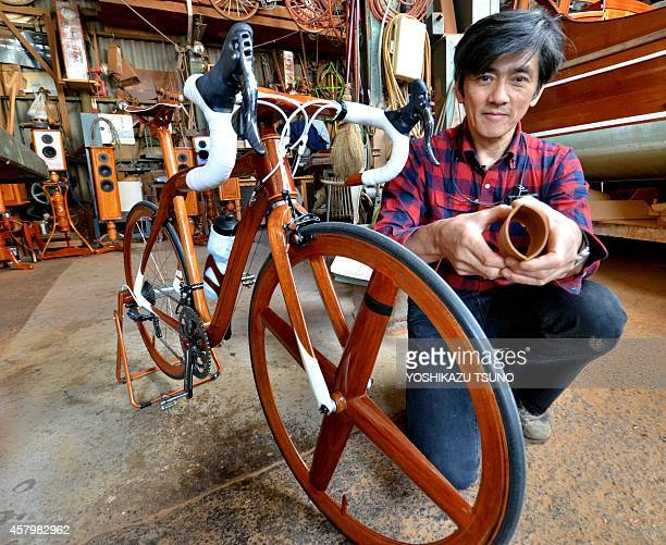 WITH 'JAPANLIFESTYLEFASHIONLEISUREBIKE' BY Japanese traditional boat builder Sueshiro Sano holds a wooden made part his bicycle built from mahogany...