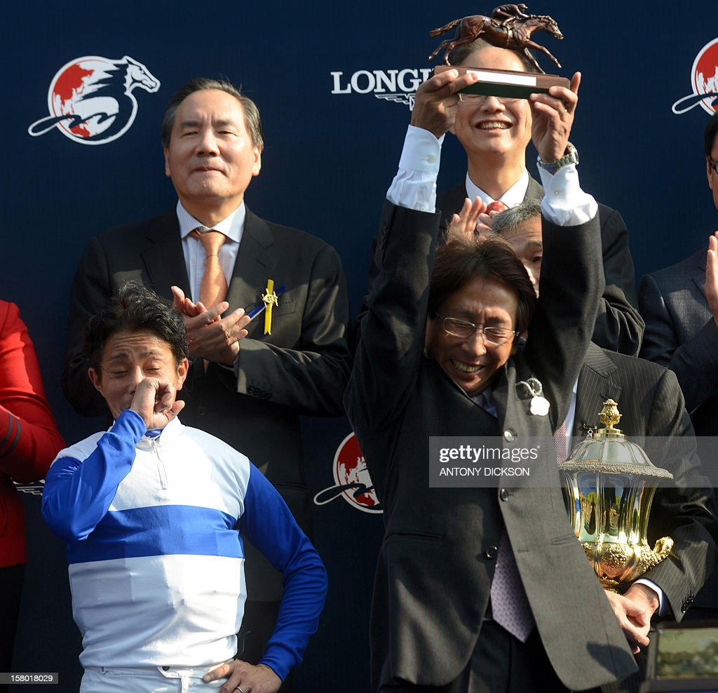 Japanese trainer Takayuki Yasuda (front R) and jockey Yasunari Iwata (front L) celebrate after their horse Lord Kanoloa rode to victory in the 1200-metre Longines Hong Kong Sprint race during the Hong Kong International Races at the Shatin racecourse in Hong Kong on December 9, 2012. The Sprint race is one of four Group One contests that are taking place at the Longines Hong Kong International Races with total prize money for the day at 9.2 million USD. AFP PHOTO / Antony DICKSON