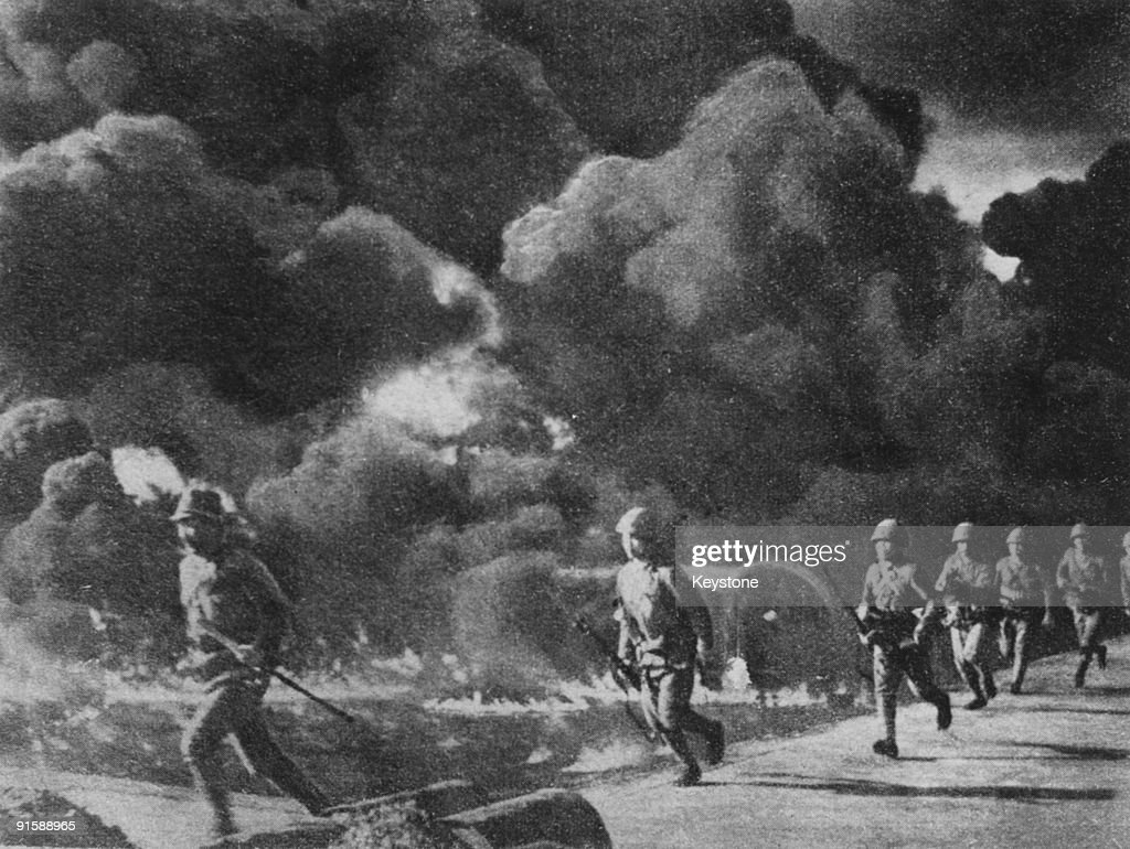 Japanese troops advancing through burning oil fields set alight by retreating American forces Philippines 1942