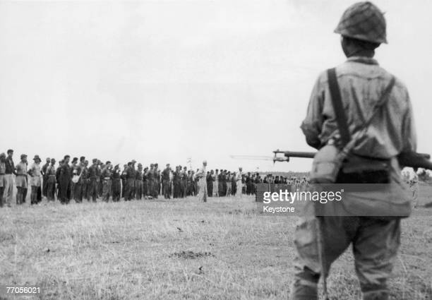 Japanese troops guard American and Filipino prisoners in Bataan in the Philippines after their capture of the Bataan Peninsula on 9th April 1942 The...