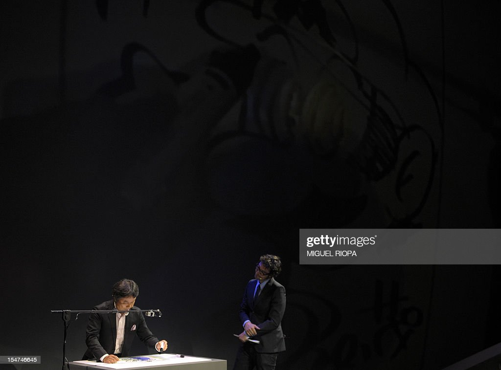 Japanese video game designer Shigeru Miyamoto (L) draws the arcade game star Mario Bros at the Jovellanos Theatre in Gijon, on October 25, 2012, to participate in a tribute to the video game, on the eve of the Prince of Asturias 2012 Award ceremony. Miyamoto has been awarded with the Prince of Asturias Award for Communication and Humanities.