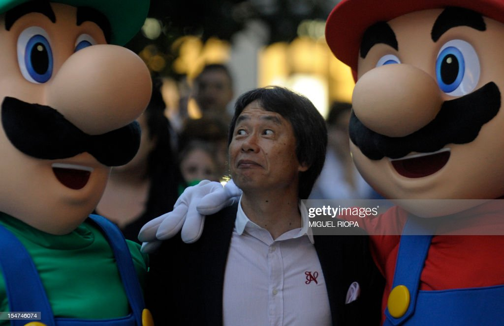 Japanese video game designer Shigeru Miyamoto (C) grimaces as he poses with arcade game stars Mario Bros and Luigi at the Jovellanos Theatre in Gijon, on October 25, 2012, to participate in a tribute to the video game, on the eve of the Prince of Asturias 2012 Award ceremony. Miyamoto has been awarded with the Prince of Asturias Award for Communication and Humanities. AFP PHOTO/ MIGUEL RIOPA