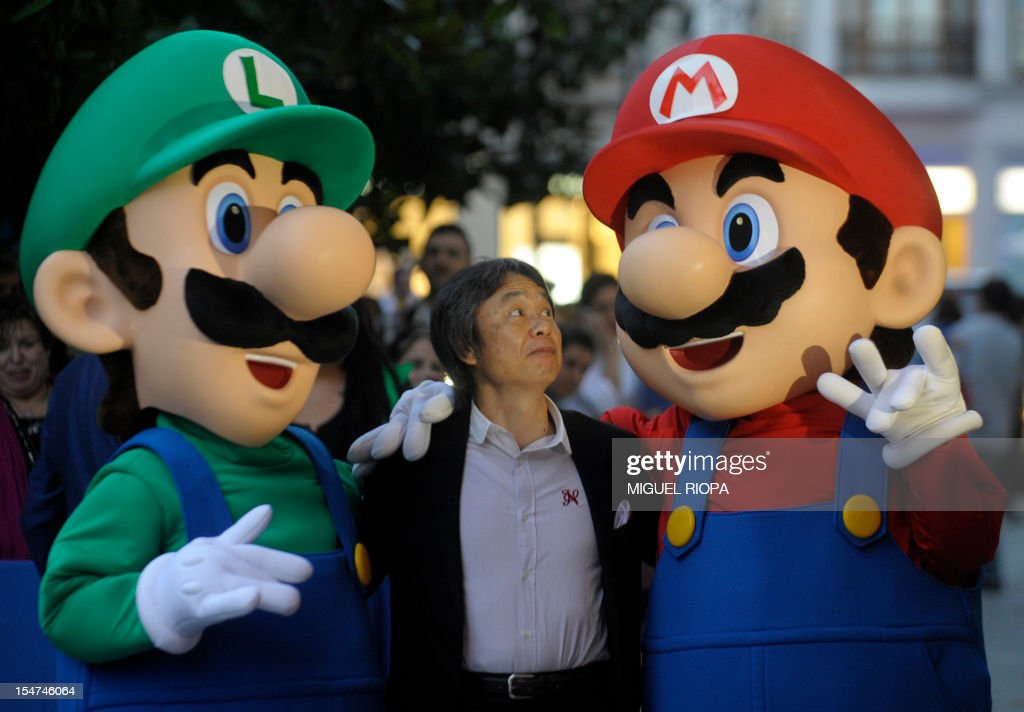 Japanese video game designer Shigeru Miyamoto (C) poses with arcade game stars Mario Bros and Luigi at the Jovellanos Theatre in Gijon, on October 25, 2012, to participate in a tribute to the video game, on the eve of the Prince of Asturias 2012 Award ceremony. Miyamoto has been awarded with the Prince of Asturias Award for Communication and Humanities.