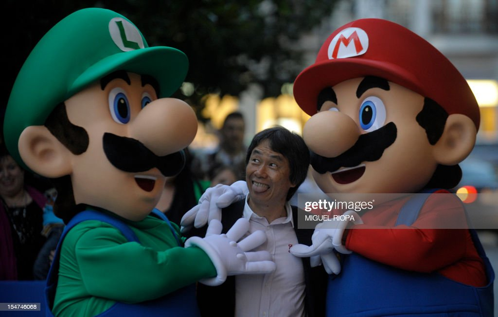 Japanese video game designer Shigeru Miyamoto (C) sticks out his tongue as he poses with arcade game stars Mario Bros and Luigi at the Jovellanos Theatre in Gijon, on October 25, 2012, to participate in a tribute to the video game, on the eve of the Prince of Asturias 2012 Award ceremony. Miyamoto has been awarded with the Prince of Asturias Award for Communication and Humanities.