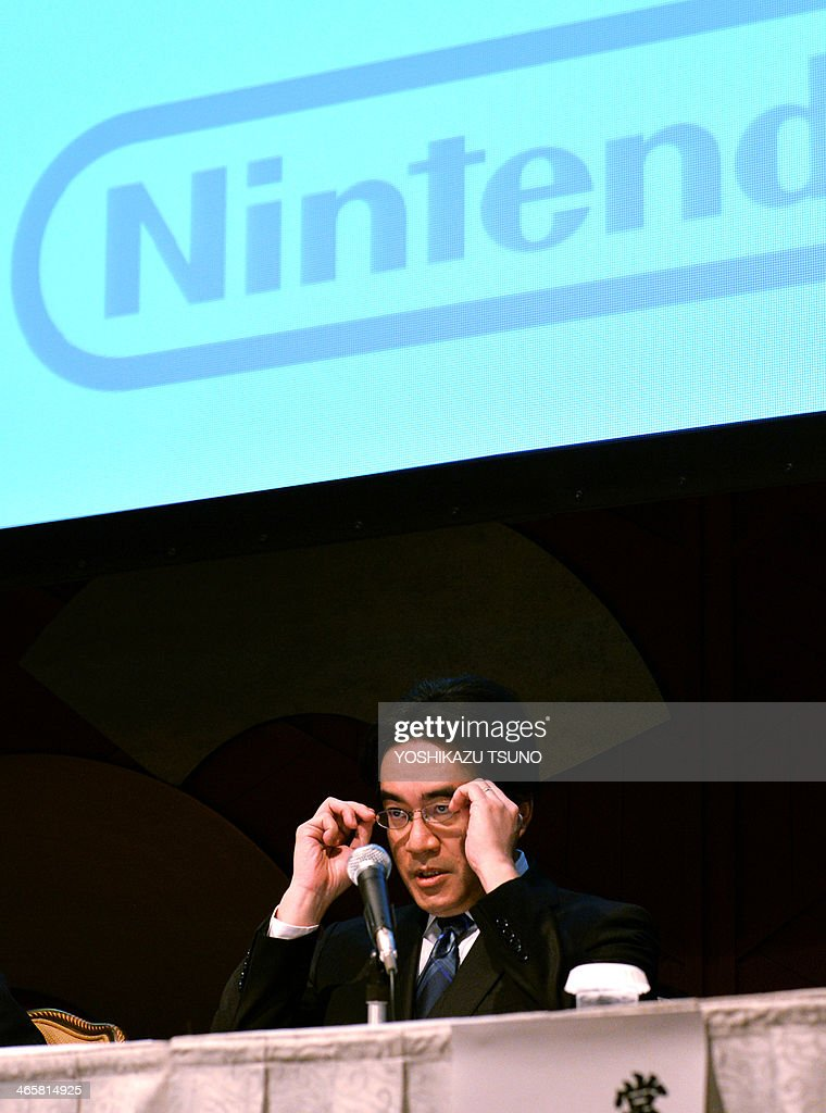 Japanese video game giant Nintendo president Satoru Iwata adjusts his gallses as he announces the company's business strategy in Tokyo on January 30, 2014. Iwata will slash his salary in half after announcing a 30 percent dive in nine-month profit on weak demand for its new Wii U video game console as gamers are enticed by cheap, downloadable games for mobiles. AFP PHOTO / Yoshikazu TSUNO