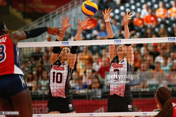 Japanese volleyball players Koyomi Tominaga and Nana Iwasaka try to block a smash during their match against the Dominican Republic during the women...