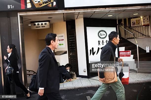 Japanese walk past a homeless man squating on the corner of a street in Tokyo on November 1 2016 Japan's central bank again pushed back the timeline...