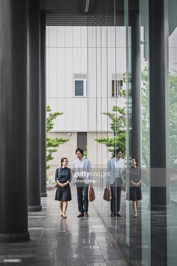 Japanese woman and male colleague outside modern office building