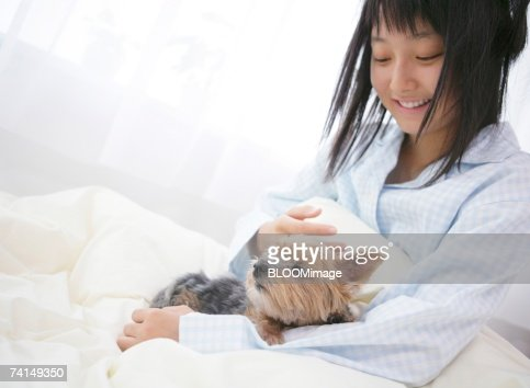 Japanese woman beside dog in bed in the morning stock for Dog bed beside bed