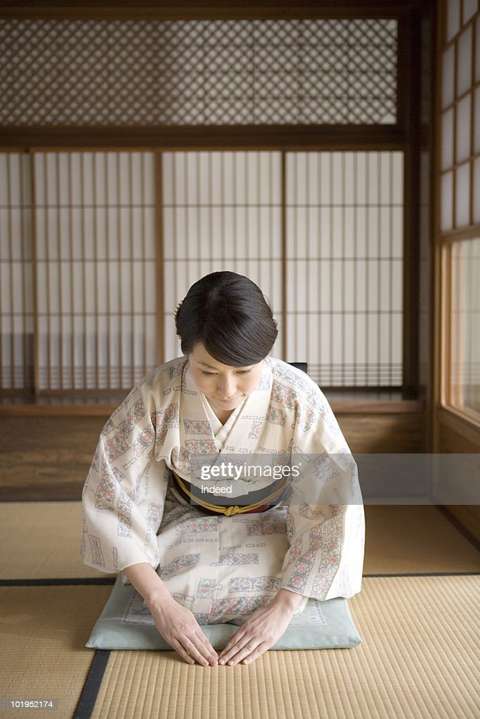Japanese woman bow her head sitting on Tatami mat