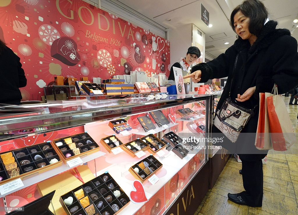 A Japanese woman buys chocolate of Belgium's famous brand Godiva at Tokyo's Takashimaya department store on February 13, 2013, one day before Valentine's Day. Japanese women thronged department stores to buy Valentine's Day chocolates boosting a sector worth over 11 billion USD a year. AFP PHOTO / Yoshikazu TSUNO