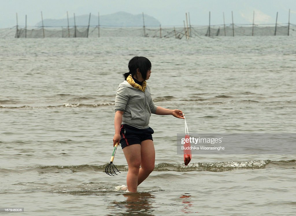 A Japanese woman carries freshly harvest shell bag as she walks along Shinmaiko beach on May 3, 2013 in Himeji, Japan. Shell collecting are one of most famous pleasure events around the country during the longest spring holiday known as 'Golden Week'. Japan holds the Golden Week holidays from April 28 to May 6, during that period millions of Japanese people travel to tourist attractions.