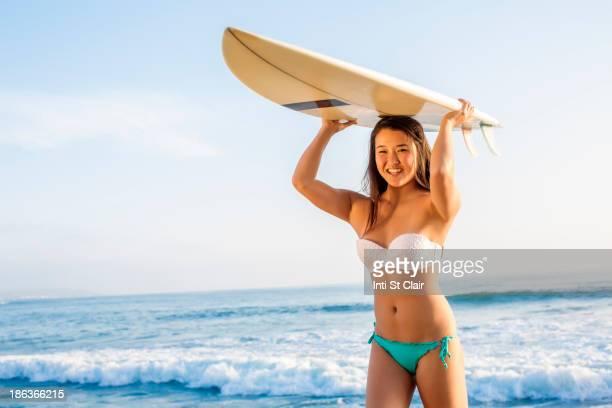 Japanese woman carrying surfboard overhead on beach