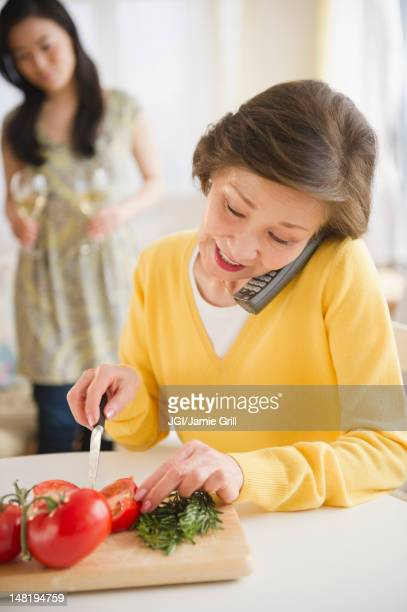 Japanese woman cutting vegetables and talking on telephone