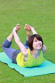 Portrait of Japanewe woman doing yoga exercise outdoor