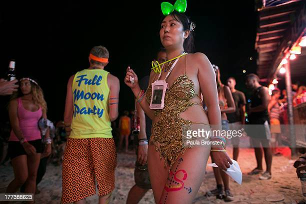 Japanese woman dressed in costume attends the full moon party on the beach of Haad Rin on August 22 2013 in Koh Phangan Thailand Thousands of people...