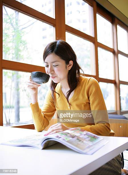 Japanese woman drinking and reading a book