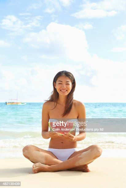 Japanese woman eating watermelon on beach