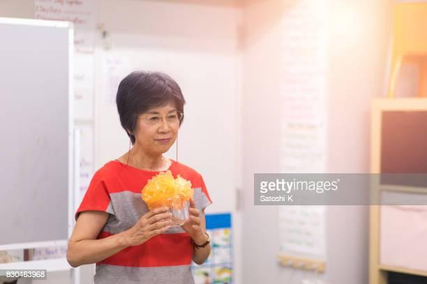 偽花の花束を保持している語学学校でスピーチを与える日本の女性