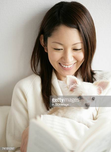 Japanese woman holding dog with reading book