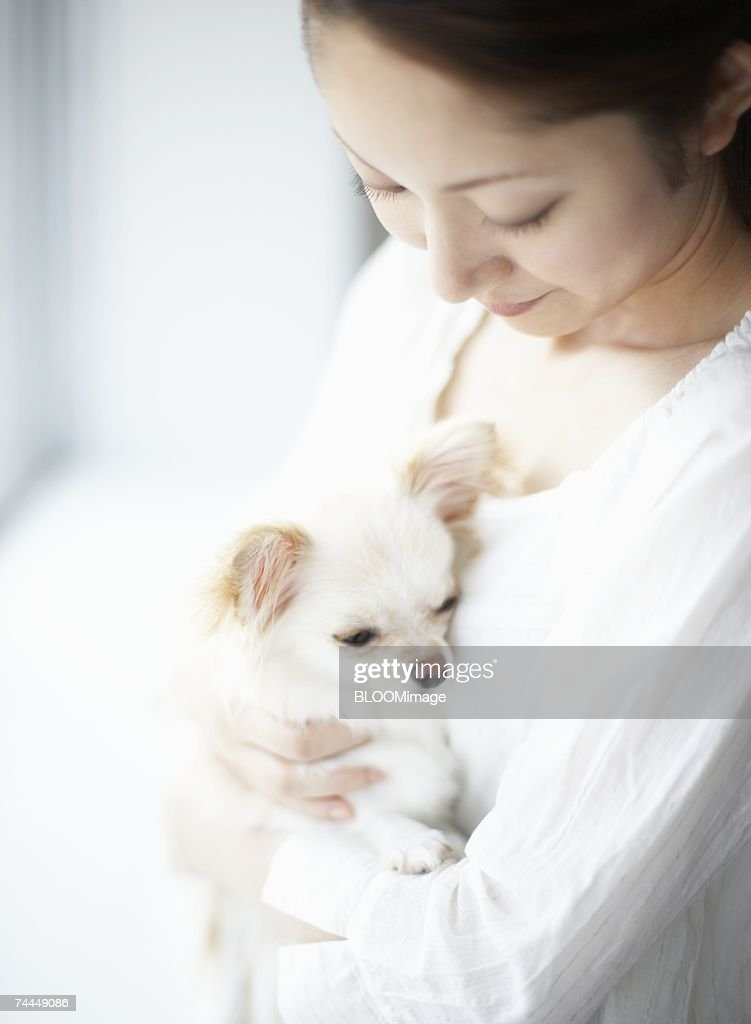 Japanese woman holding dog with sitting on sofa