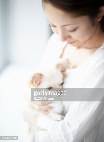 Japanese woman holding dog with sitting on sofa