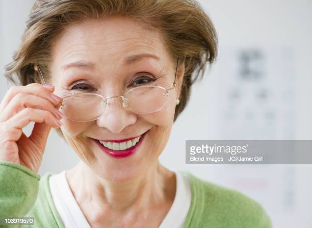 Japanese woman holding eyeglasses