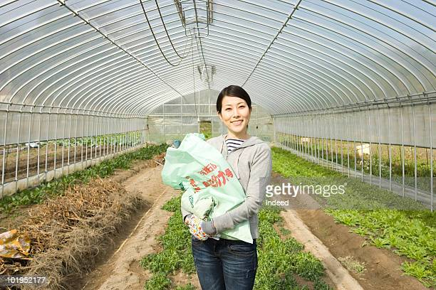 Japanese woman holding fertilizer bag