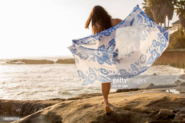 Japanese woman holding sarong on beach