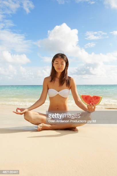 Japanese woman holding watermelon and meditating on beach