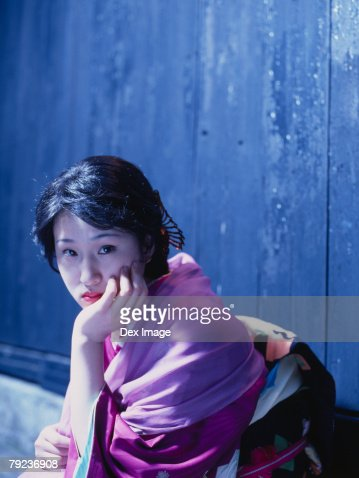 Japanese woman in kimono crouching against wall : Stock Photo