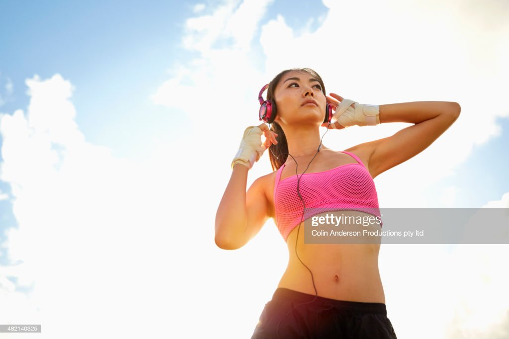 Japanese woman in sports-bra listening to headphones outdoors