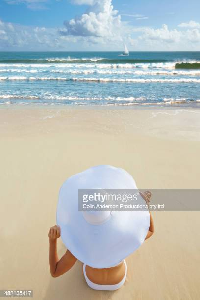 Japanese woman in sun hat sitting on beach