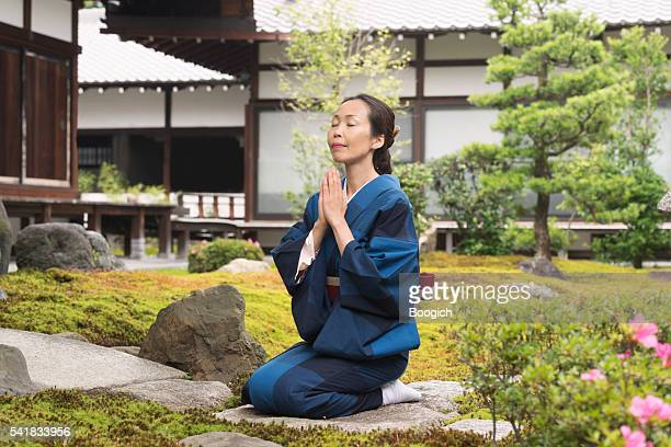 Japanese Woman in Traditional Kimono Praying at Temple Kyoto Japan