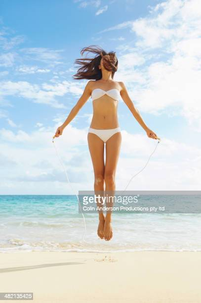 Japanese woman jumping rope on beach