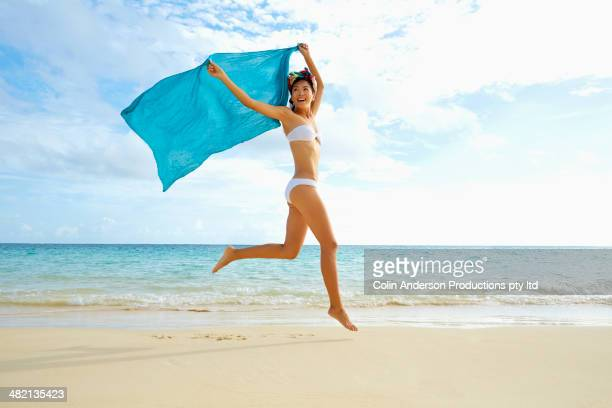 Japanese woman jumping with sarong on beach