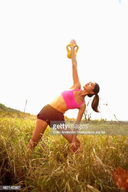 Japanese woman lifting kettle bells in rural field