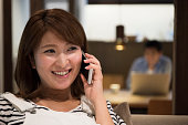 Japanese woman listening on mobile phone, smiling