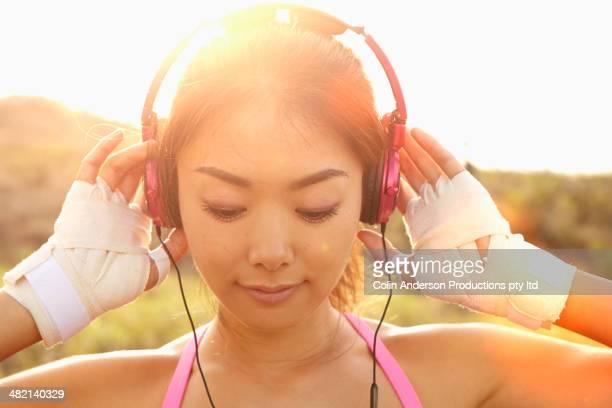 Japanese woman listening to headphones outdoors