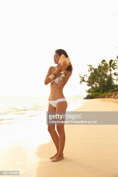 Japanese woman listening to seashell on beach