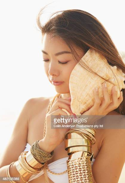 Japanese woman listening to seashell