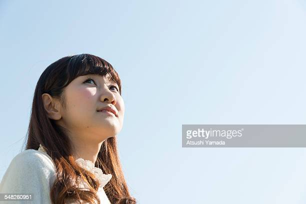 Japanese woman looking away,sky background