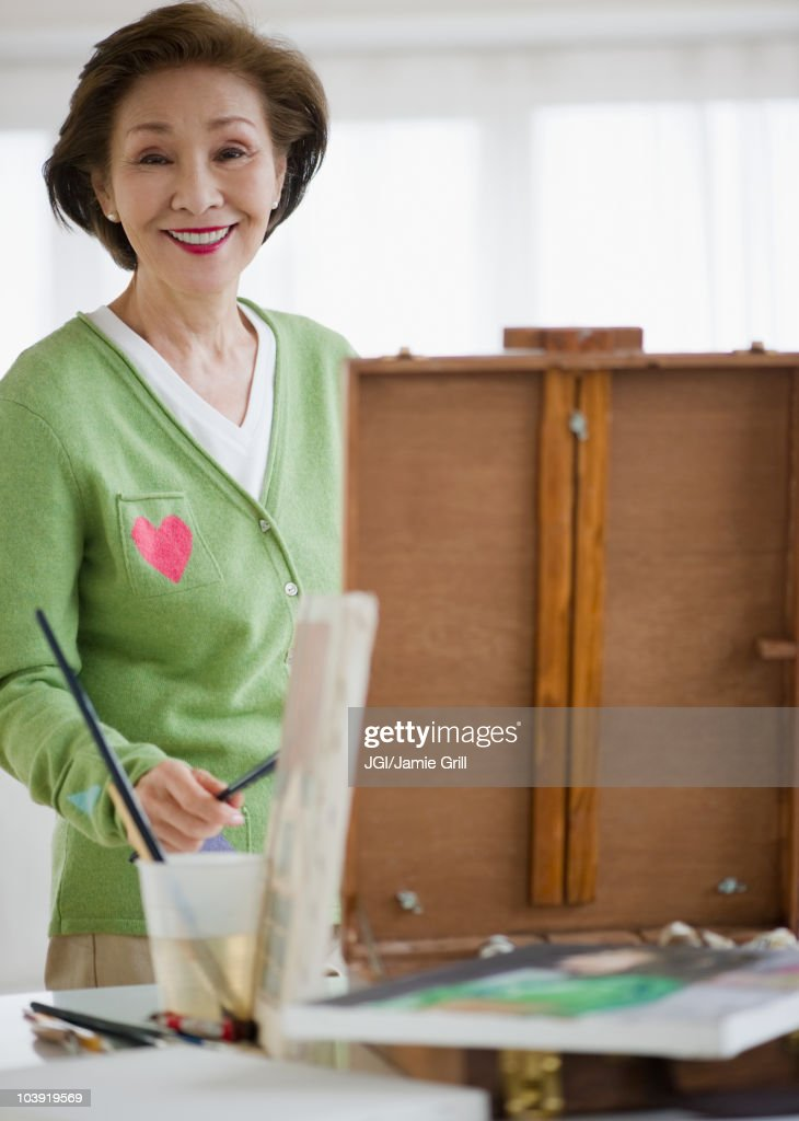 Japanese woman painting on easel : Stock Photo
