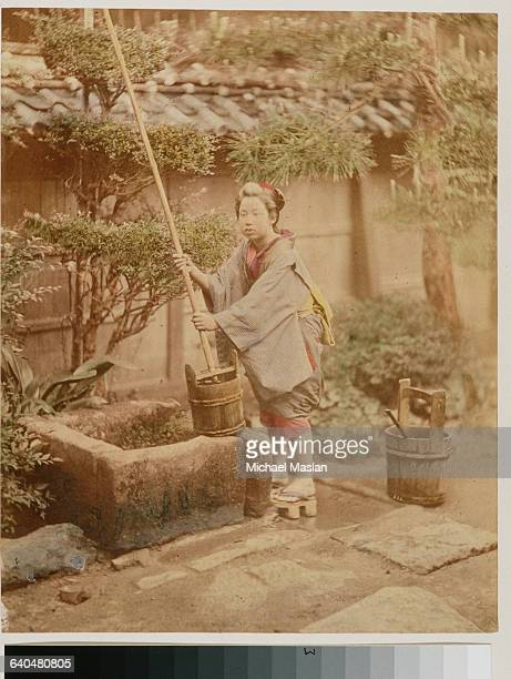 A Japanese woman places a mop into a bucket near what seems to be a well in an outside garden Japan ca 1890s