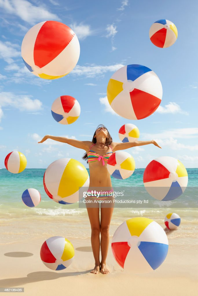Japanese woman playing with balls on beach