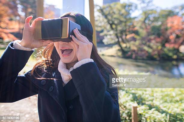 Japanese woman playing with vitural reality simulator in the morning