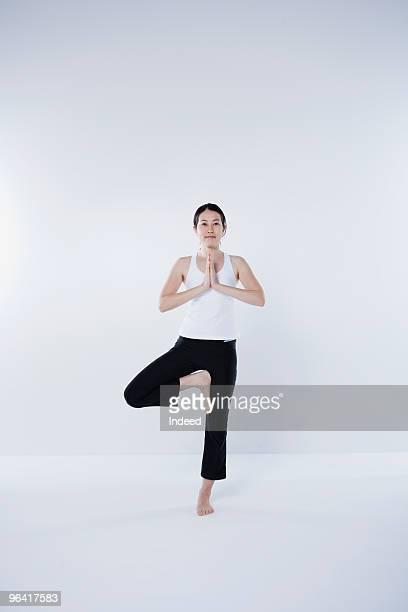Japanese woman practicing yoga - tree pose