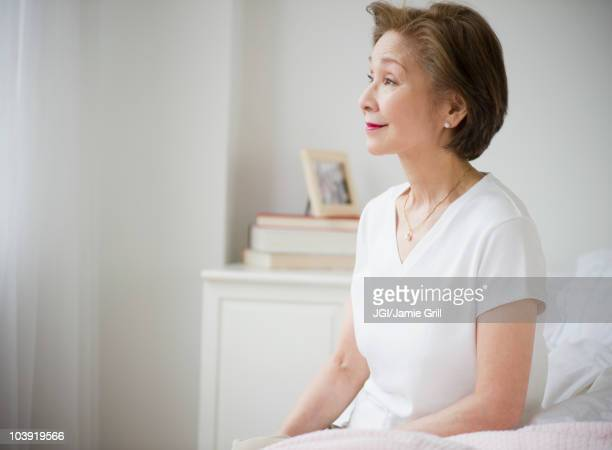 Japanese woman sitting on bed