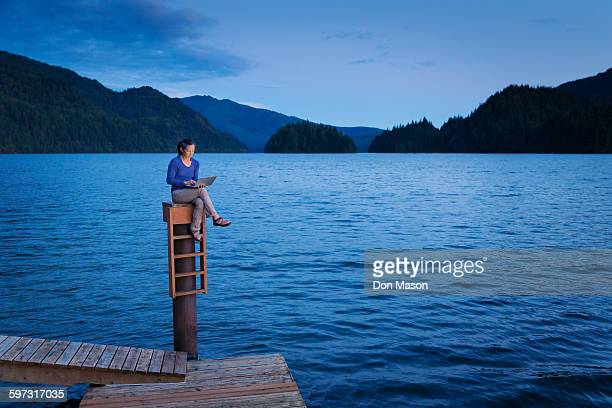 Japanese woman sitting on wooden dock at lake