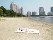 Japanese woman sleeping on futon, at beach